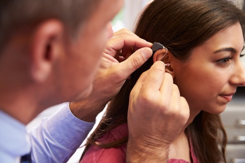 Doctor putting a hearing aid on a girl