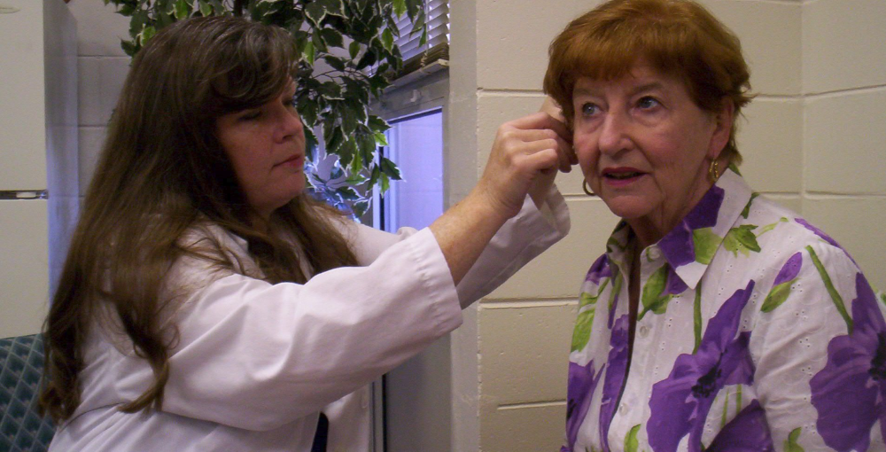 Doctor placing hearing aids on a lady